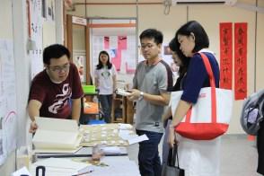 同学向中文系系友进行文字展览的解说。