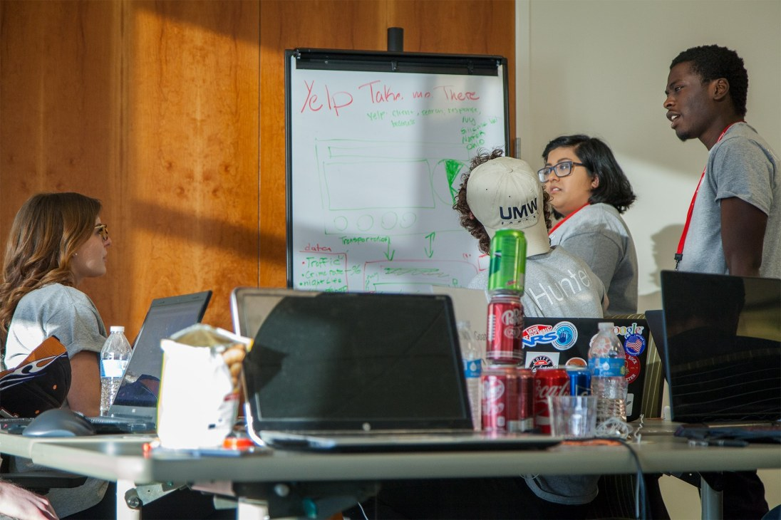 Mikaela Goldrich, Hunter Renard, Anum Qureshi, andJosh Mwandu from Team Goats work through a challenge at HackU 5. The team won the Best Open Source Project category and took home Amazon Dots.