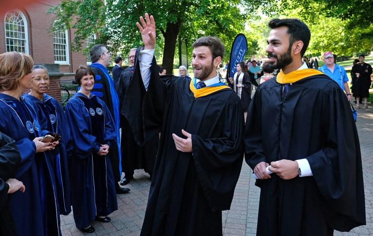 Davis, left, and Haider share a light moment with faculty before the procession.