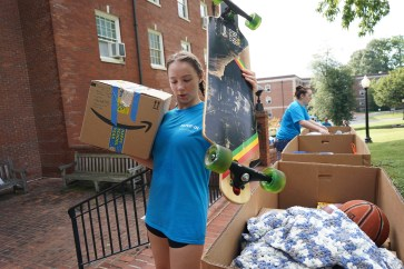 A volunteer carries a student's belongings to their residence hall. First-years brought everything from bedding, clothes and shower caddies, to skateboards, handmade quilts and sports equipment. Photo by Suzanne Rossi.