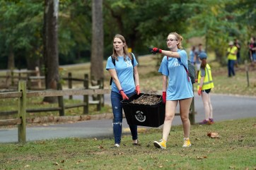 Eliza Van Essendelft (left) and Carolyn Willmore haul leaves at Fredericksburg's Old Mill Park during this Saturday's Into the Streets event. Photo by Suzanne Carr Rossi.