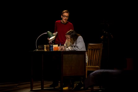 Playing Bechdel at age 43, Olivia Whicheloe (standing) observes her college-aged self, played by Lydia Hundley (seated). Both seniors, Whicheloe and Hundley are one of three actors playing graphic memoirist Alison Bechdel in 'Fun Home.' Photo by Geoff Greene.