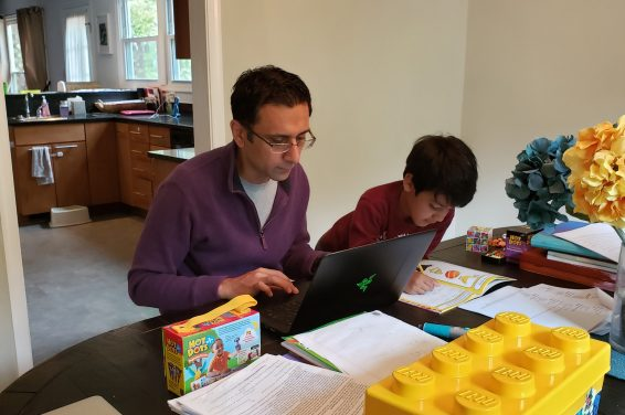 Kashef Majid, an associate professor in the College of Business, grades marketing papers in the workspace he shares with his son.