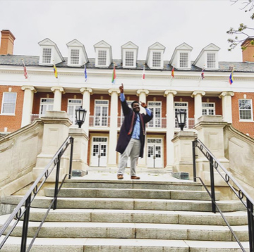 2020 graduate Jeremiah Ward celebrates completing his bachelor's degree in psychology on the steps of Lee Hall. Ward was the 2020 recipient of the Clara Boyd Wheeler Award at UMW's virtual Eagle Awards.