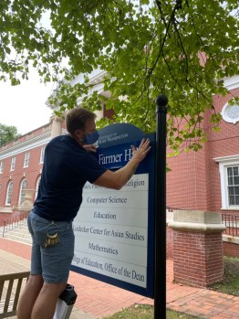 Facilities Services' Micy Wallace changes the sign outside Trinkle Hall, renamed today as James Farmer Hall. With the vote by UMW's BOV to rename the building, a beloved member of the Mary Washington community who spent most of his career fighting injustices, is memorialized.