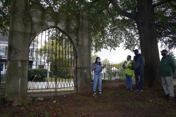 Freshman Eliza Vegas shows off the massive iron City Cemetery gate, constructed by local iron workers and stone masons. Photo by Suzanne Carr Rossi.