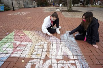 First-year student Kylie Jackson (left) and sophomore Grayson Collins (right) chalk Campus Walk on Saturday as part of the MLK Day of Service. Photo by Suzanne Carr Rossi.