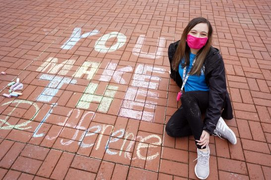 """""""I wanted to share a message that everyone can relate to, and hopefully, it will speak out to people in need of a little encouragement,"""" said sophomore Grayson Collins, who spent UMW's MLK Day of Service chalking Campus Walk with positive messages. Photo by Suzanne Carr Rossi."""