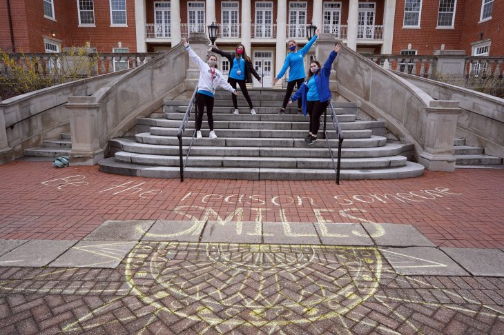 From left to right, Kylie Jackson, Grayson Collins, Charlotte Russell and Kayla Kippes with the chalk messages they created in front of Lee Hall as part of the MLK Day of Service. Photo by Suzanne Carr Rossi.