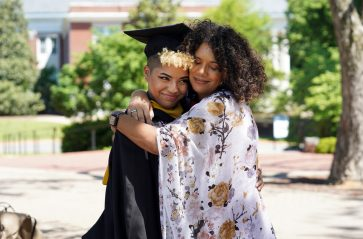 Monique Jones (right) gives her daughter, Reina Irby, a hug after one of three 2020 graduation ceremonies. Photo by Suzanne Carr Rossi.