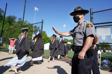Campus Police Chief Mike Hall extends waves and well wishes to graduates as they process onto the Campus Recreation Field. All of his officers played key roles in the ceremonies. Photo by Suzanne Carr Rossi.