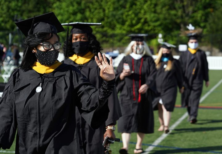 Graduates processed in from Sunken Road, waving to family and friends sitting in pods, eager to cheer them on. Photo by Suzanne Carr Rossi.