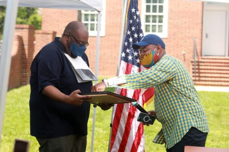 Delegate Joshua Cole (right) presents Chris Williams with House Resolution 601, commending his work with the JFMC to keep Dr. Farmer's legacy alive. Photo by Karen Pearlman.