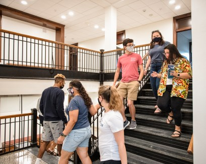 A group walks down one of the signature open stairways in Virginia Hall. The stone stairs and hardwood banisters were revived as part of a $19 million renovation to the building, whose construction began in 1914. Photo by Tom Rothenberg.