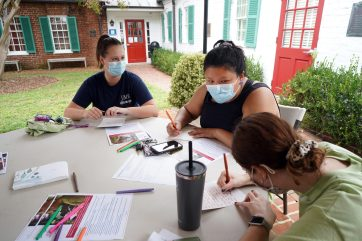 From left to right, Abigail Wood, Ashleigh Liang Foster and Mallory Karnei write notes to servicemembers, military families and local veterans at the James Monroe Museum. Photo by Suzanne Carr Rossi.