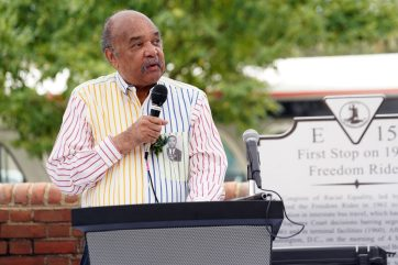 Freedom Rider Dion Diamond speaks to the crowd gathered for the unveiling of the marker, while wearing his mug shot from the Freedom Rides pinned to his shirt. He spent two years participating in the protests to desegregate interstate travel. Photo by Suzanne Carr Rossi.