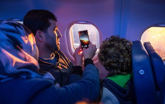 Una familia mira por la ventana del avión y toma fotos mientras viajan a su nuevo hogar. Foto: OIM / Muse Mohammed