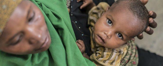 Un jeune garçon souffrant de malnutrition porté par sa mère dans un centre de programme thérapeutique ambulatoire soutenu par l'UNICEF à Baidoa, en Somalie. Photo: UNICEF / Mackenzie Knowles-Coursin