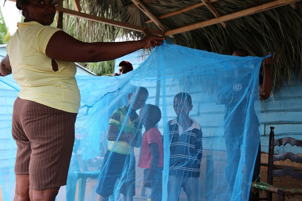 Photo: Children surrounded by protective malaria net in the Dominican Republic.