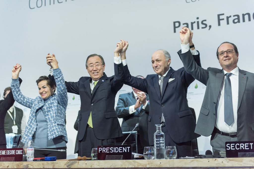 """Photo: On 12 December 2015, the 196 parties to the UN Framework Convention on Climate Change (UNFCCC) adopted the Paris Agreement. Secretary-General Ban Ki-moon (third right) called the negotiations the """"most complicated, most difficult, but most important for humanity."""" Also pictured, UNFCCC's Christiana Figueres; French Foreign Minister Laurent Fabius and President of the UN Climate Change Conference (COP21); and French President François Hollande (right). UN Photo/Mark Garten"""
