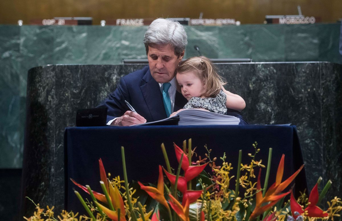 U.S. Secretary of State John Kerry signing the agreement with his granddaughter on his lap. UN