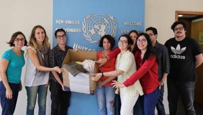 UN Staff in Rio holding donated clothes.