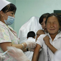 A young girl is immunized against measles at a school in Mongolia.