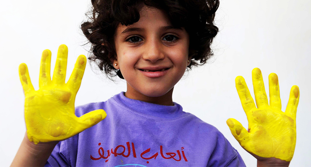 A girl shows the paint in her hands