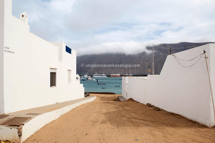 Isla Graciosa: casette bianche, terra battuta ed in fondo l'azzurro del mare e le scogliere nere, tutti i colori di Lanzarote.