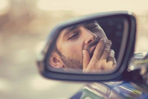 Side mirror view reflection sleepy tired fatigued yawning exhausted young man driving his car in traffic after long hour drive. Transportation sleep deprivation accident concept