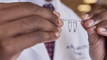 Dr. Musunuru  sujetando muestra de plasma sanguíneo. La técnica CRISPR modificada, ofrece pistas para imitar mutaciones genéticas protectoras.