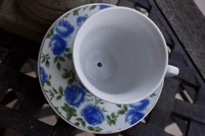 Tasse à thé percée et transformée en mangeoire à oiseaux