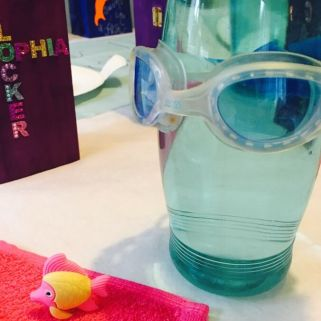 Swim party theme decorations. Use items you have at home to create a swim scene at your dinner table. Flannels as placemats and blue water bottles with spare goggles attached.