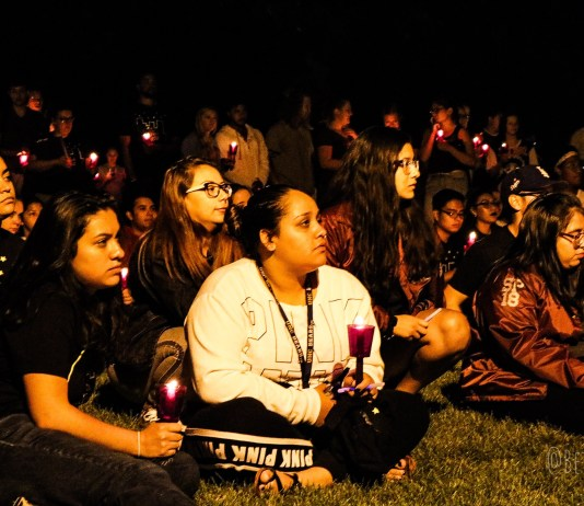 A group of attendees sit on the lawn on central campus.
