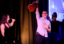 Jason Loing hoists his ukulele above his head, smiling on stage