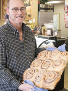Jimmy holding up their cinnamon rolls at Jimmy's Round-Up Cafe - photo by Dennis Spielman