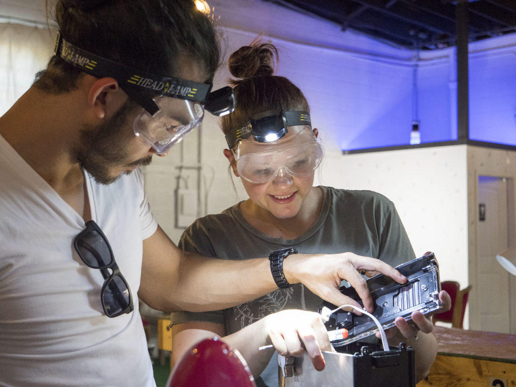 A couple takes apart a machine at CHAOS - photo by Dennis Spielman