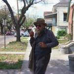Poppa Neutrino walking down a suburban street wearing a hat