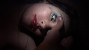 A passed out girl has her eyelid opened