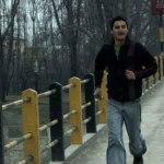 Kashmir man runs across a bridge