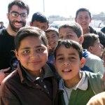 Filmmaker Usama Alshaibi stands with Iraqi children at an outdoor market