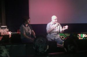 Mike Plante interviews Jeff Krulik on stage of a movie theater