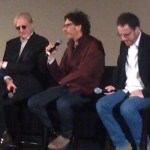 Joel Coen answers a question on stage, flanked by Ethan Coen and T-Bone Burnett