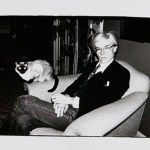 Artist Andy Warhol sits in a chair with a siamese cat