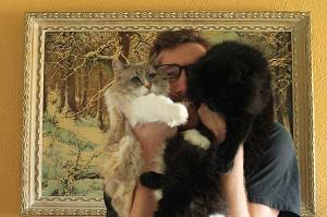 Filmmaker Ben Popp holds his two cats, one white and one black, up to his face
