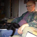 Filmmaker Jeff Krulik tries to work on his laptop while his black cat Iggy sleeps on his legs