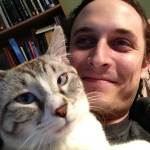 Aaron Zeghers relaxes with his white and gray cat Baby on his chest
