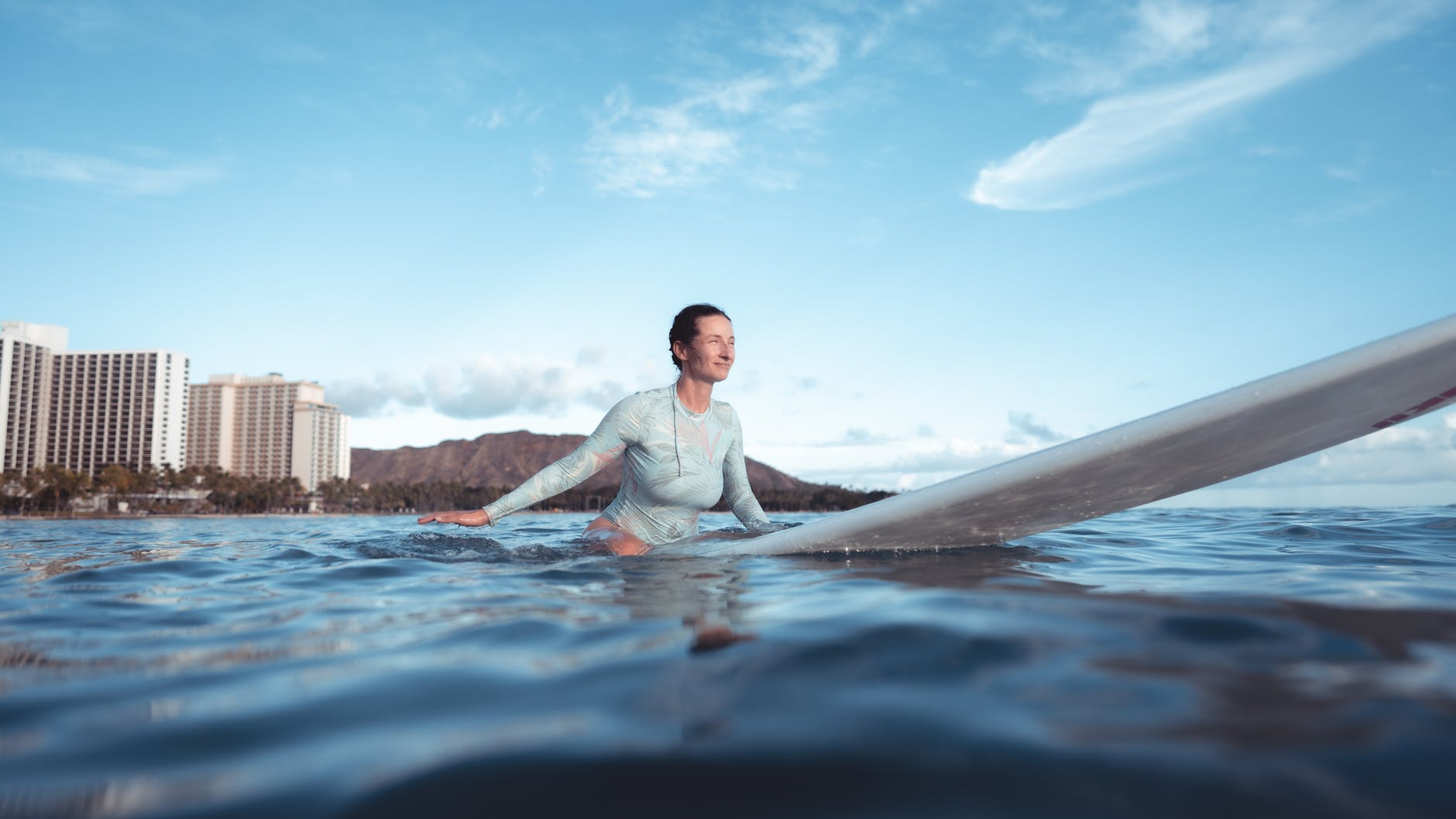 sporty young lady sitting on surfboard in ocean