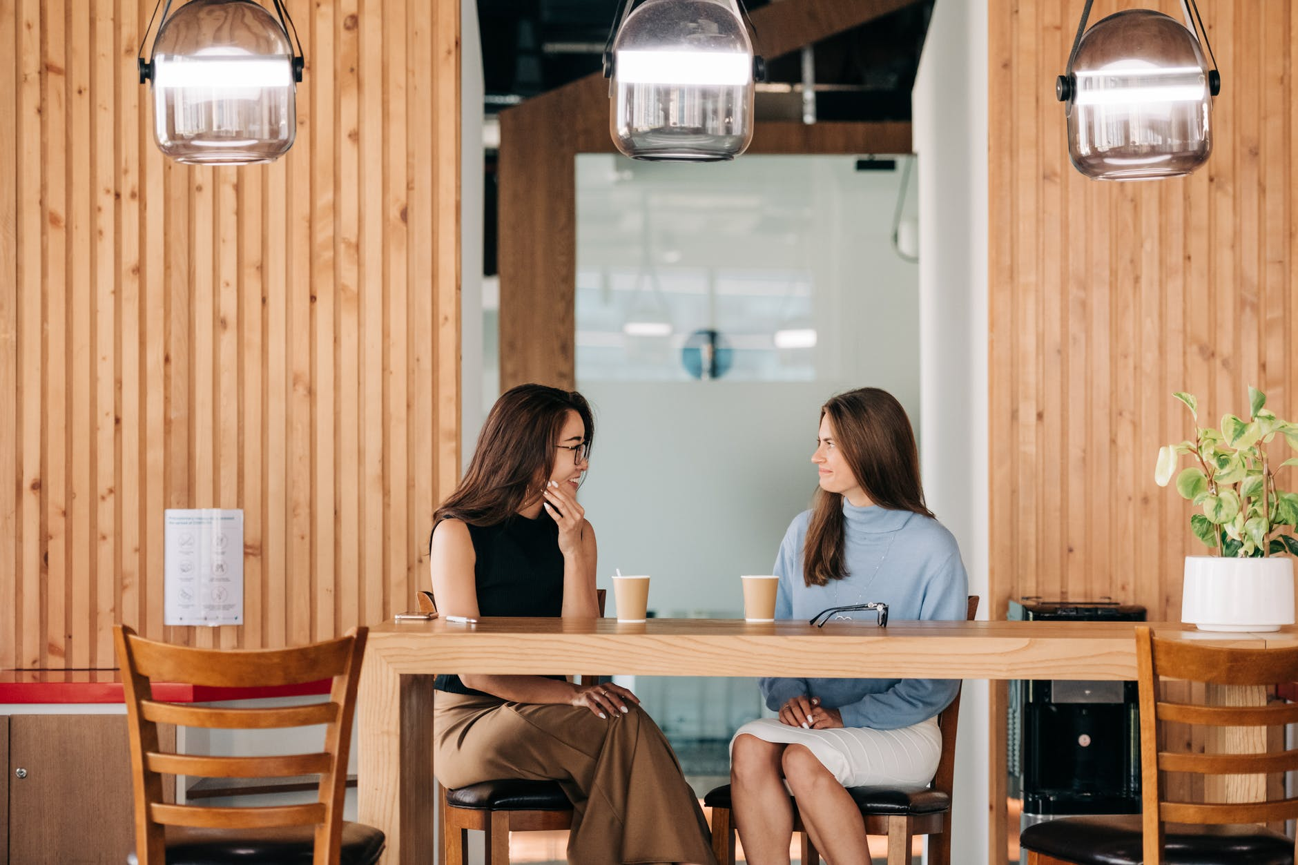cheerful diverse friends talking at table with coffee in cafe