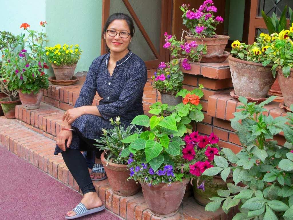 Dr. Padma Bajracharya on the stairs outside of Moksha Ayurveda & Panchakarma Center | © Rachel Jones